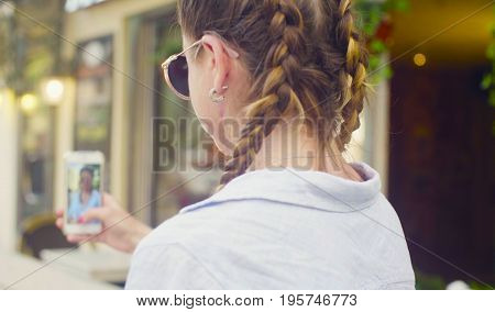 Close up portrait of young woman in sunglasses shooting sefie