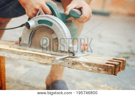 A modern green circular cutting wooden table in the workshop. A close-up of a circular saw