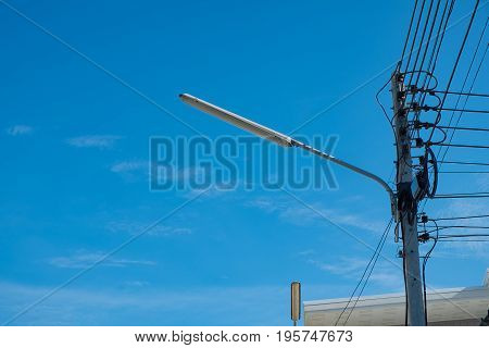 Street Light Lamp With High Voltage Power Pole And Wires Tangled Against The Blue Sky.