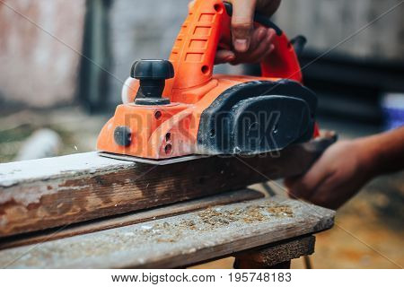 Close up of the hand of an man planing a plank of wood in his carpentry workshop with a plane to smooth the surface