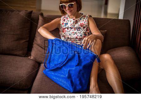 Young glamour woman wearing flower dress posing with luxury handmade snakeskin python handbag. Beautiful stylish girl holding handbag and looking away.
