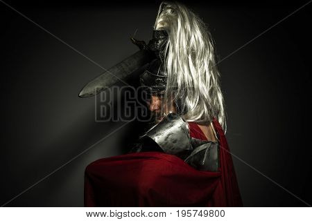 Roman centurion with armor and helmet with white chalk, steel sword and long red cape