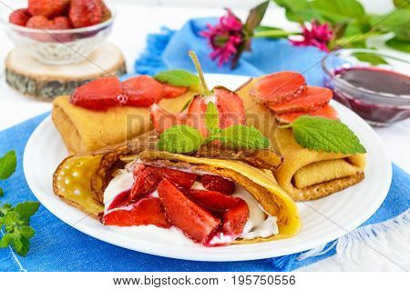 Openwork pancakes with a delicate curd cream (ice cream) and fresh strawberries mint on a plate.