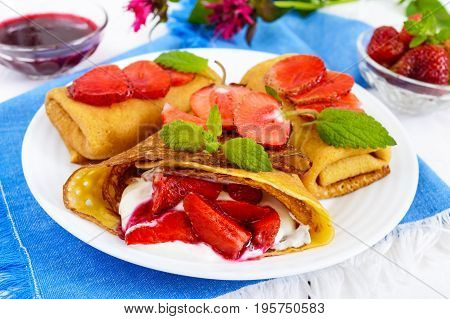 Openwork pancakes with a delicate curd cream (ice cream) and fresh strawberries, mint on a plate.