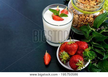 A set of a product for a delicious healthy breakfast: granola yogurt fresh strawberries green mint leaves on a black background. Proper nutrition. Dietary menu.