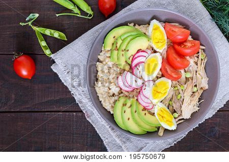 Useful breakfast: oatmeal with rabbit meat avocado boiled egg tomatoes radish green peas flax seeds. Top view. Proper nutrition.