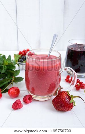 Berry smoothie in of glass cups fresh berries on white wooden background. Proper nutrition. Healthy breakfast. Dietary menu.