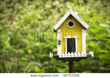 Little yellow birdhouse on stand in the middle of a garden