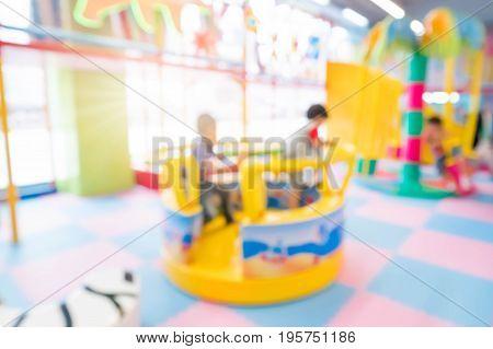 Abstract blur happy kids playing on slide Indoor children playground.