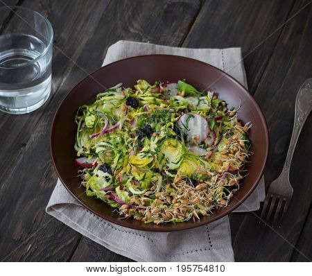 Salad from brussels sprouts with radish raisins and sprouts of wheat. Healthy diet detox food. On a wooden background in a rustic style. Selective focus