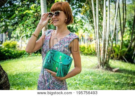 Outdoor fashion portrait of glamour sensual young stylish lady in sunglasses with luxury handmade snakeskin python bag. Python handbag. Sunny day, green plants, tropical palms. poster