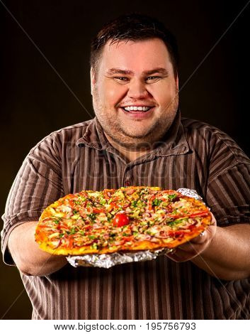 Fat man eating fast food and offers great pizza to customers and friends. Breakfast for overweight person. leads to obesity. Person regularly overeats concept on dark background.