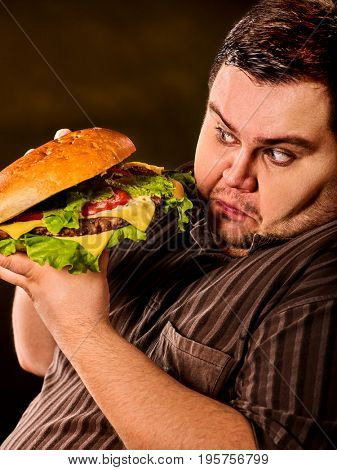 Man eating fast food hamberger. Fat person with brutal look made great huge hamburger and admires him, intending to eat it. Junk meal leads to obesity. Person regularly overeats concept .