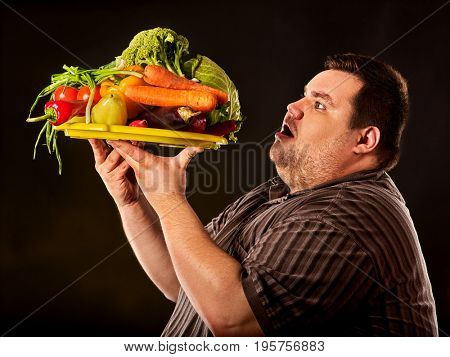 Diet fat man eating healthy food with vegetables cauliflower and sweet pepper with radish , tomatoes for overweight person. Male trying to lose weight first time on dark background.