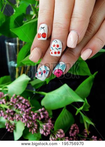 Summer manicure with summer berries for a young woman and a branch of lilac in the background