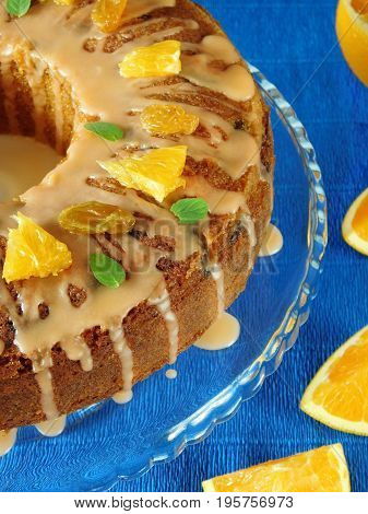 Orange cake covered with icing and topping surrounded by slices of orange on a blue background