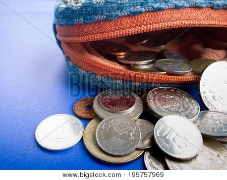open purse with international coin on the blue background