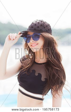 A young girl in a black cap, a black bathing suit and blue sunglasses stands on the beach background, looks at the camera.