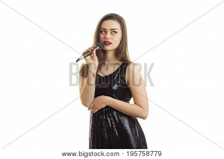 Cute young brunette in black dress sings a sing with microphone and looking away isolated on white background