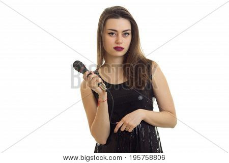 young brunette in black dress sings a sing with microphone and looking at the camera isolated on white background