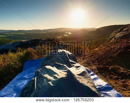 Beautiful Awakening In A Sleeping Bag On  Rock Ledge. Birds Are Singing And Sun At Horizon.