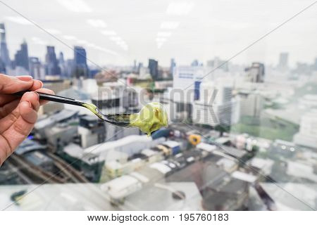 close up woman with plastic spoon with green tea ice cream with city view background
