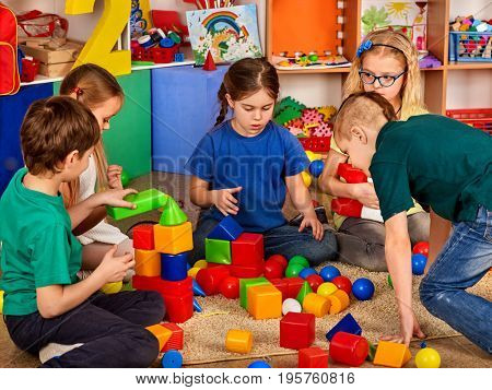 Children building blocks in kindergarten. Group kids playing toy on floor. Top view of interior preschool. Children develop their fingers in a game of cubes. Children learn to be friends in the team.