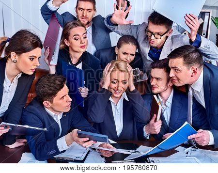 Mad business people office. Team people are unhappy with their leader. Intern woman manager holds one's hands by head does not cope with his duties. Crazy crowd in stress throw up chief's papers.