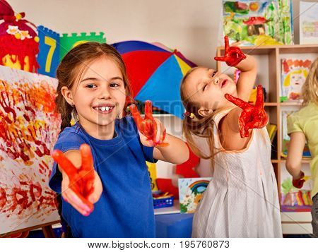 Children painting finger on easel. Small students in art school class. Sisters play in kindergarten. Craft drawing education develops creative abilities of children.