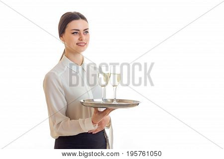 Cheerful waitress in uniform with trey in hands smiling isolated on white background