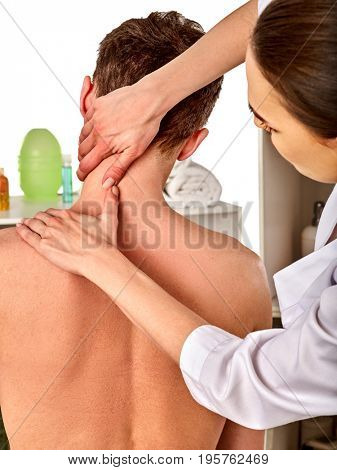 Shoulder and neck massage for woman in spa salon. Doctor making neck therapy in rehabilitation center . Direction of dislocation in clinic. Back view. Straightening of the shoulder dislocation.