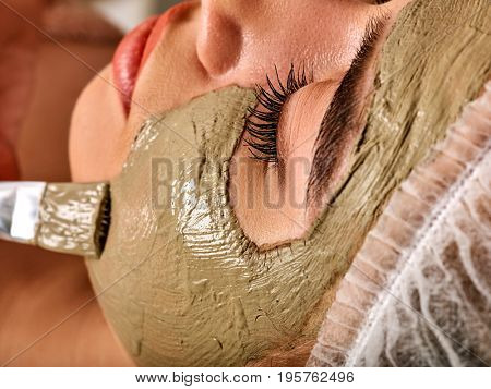 Mud facial mask of woman in spa salon. Massage with clay full face. Girl on with therapy room. Beautician with brush therapeutic procedure. Mask made of healing clay, close-up.