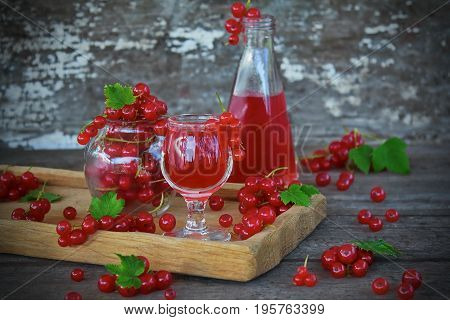 liqueur of red currant in the glass and fresh berries on the old background