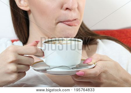 Young smiling girl drinking coffee and lick one's lips