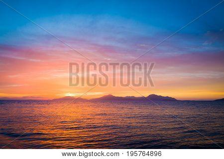 Wonderful sunset behind mountains peak protruding from ocean.