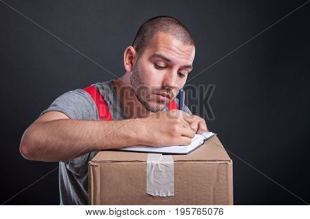 Mover Guy Writing On Agenda On Cardboard Boxes