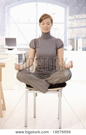 Attractive female office worker sitting at lotus position, meditating with closed eyes.?