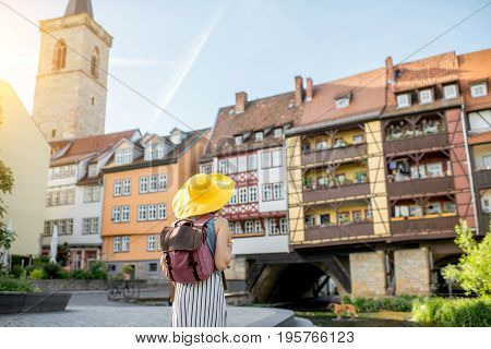 Young woman tourist in yellow hat standing back on the famous Merchants bridge background in Erfurt city, Germany
