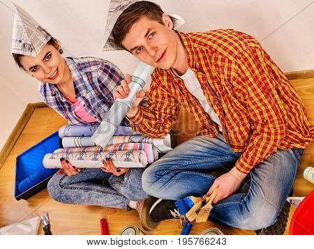 Repair family by happy couple building home using spirit level to measure. Woman and man in newspaper cap renovation apartment. Newlyweds in the new apartment.