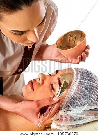 Mud facial mask of woman in spa salon. Massage with clay full face. Girl on with therapy room. Female lying wooden spa bed. Mud mask for moisturizing the skin.