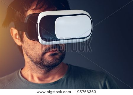 Casual bearded adult man with virtual reality VR headset indoors