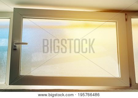Open PVC basement window with sunlight shining in