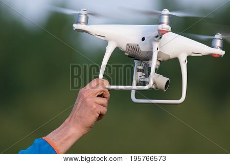 The quadcopter Landing men is catching white dron