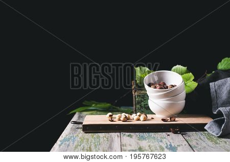 White Cup With A Filbert On A Chopping Board Over A Wooden Table