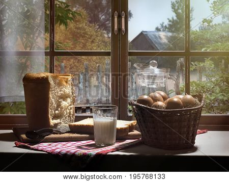 Rustic food on the window sill. A basket of eggs a glass of fresh milk. Freshly baked bread