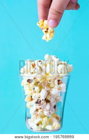 Popcorn in the glass on a blue background
