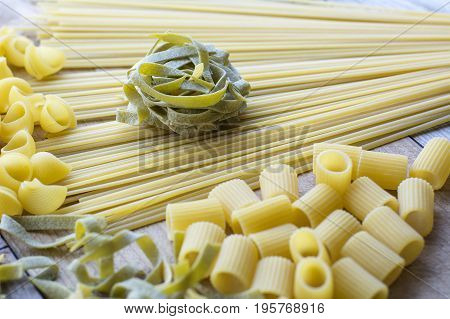 Piece of green pasta is on the yellow linguini