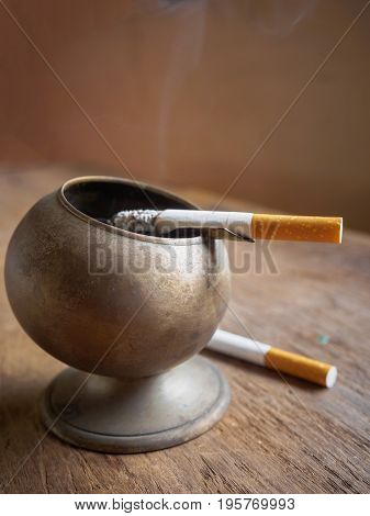 burning cigarette in brass ashtray on wooden table