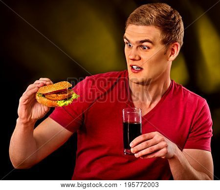 Man eating french fries and hamburger. Student consume fast food on table. Man drinks cola and dreams. Man trying to eat junk. Advertise fast food . Guy is afraid to poison himself with a hamburger