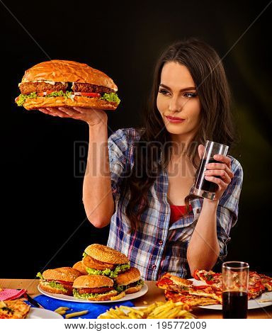 Woman eating hamburger. Student consume fast food. Girl bite of very big burger. Girl trying to eat a lot of junk. Advertise fast food on black background. Girl eat up after a diet.